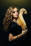 Elegance woman holding a fox fur. On a black background Royalty Free Stock Image