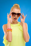Elegance woman in sunglasses on blue background. Royalty Free Stock Photos