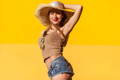 Elegance young adult model in casual clothes. Elegance young adult model in casual top, jeans short and hat. Studio shot on yellow background, outdoor Stock Photos