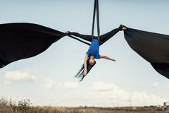Elegance young beautiful woman dance with aerial silk on a sky background. Fly yoga sport Royalty Free Stock Photo