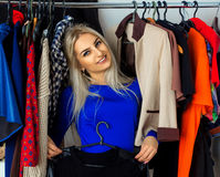 Elegance young blonde woman in clothing store smiling on camera Stock Images