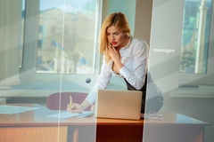 Elegance young businesswoman sitting on table in the office, usi Royalty Free Stock Image