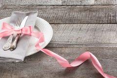 Eleganci stołowy położenie z różowym faborkiem dla romantycznego gościa restauracji na drewnianej desce nieociosany przełaz z bli Zdjęcia Stock