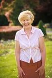 Elegancia. Elación. Mujer mayor feliz afuera con sonrisa dentuda fotos de archivo