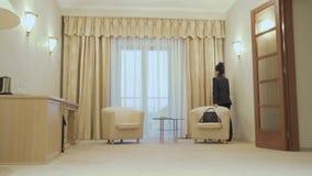 Elegancja bizneswoman opowiada na telefonie blisko okno w pokoju hotelowym zdjęcie wideo