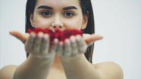 Elegancja i czułość Pięknej młodej brunetki włosiana kobieta dmucha płatki ziemia zbiory