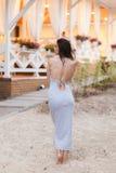 Elegancka ładna szczupła kobieta w długiej plaży smokingowy pozować blisko luksusowego kurortu blisko plaży obrazy stock