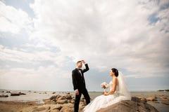 Elegancka ślub pary pozycja na dennym brzeg Nowożeńcy chodzą morzem obrazy stock