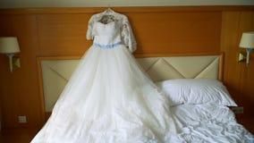 Elegancka ślubna suknia kłama na łóżku w pokoju hotelowym zbiory wideo
