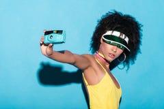 elegancka afro dziewczyna w żółtym bodysuit bierze fotografię na rocznik kamerze, Obrazy Stock