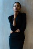 Elegancka afrykanina lub czerni Amerykańska kobieta patrzeje w dół z ręką pod podbródkiem na szarym tle Zdjęcie Royalty Free