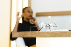 Elegancka afrykanina lub czerni Amerykańska biznesowa kobieta opowiada na telefonie przy biurem Obraz Royalty Free