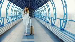 Elegancka biznesowa kobieta w białym kostiumu iść przez tunelu lub przemiany od szkła, Szczęsliwa torba na kołach zbiory wideo