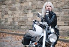 Elegancka blond kobieta pozuje z motocyklem zdjęcia stock