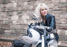 Elegancka blond kobieta pozuje z motocyklem obrazy stock