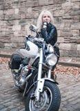 Elegancka blond kobieta pozuje z motocyklem fotografia stock