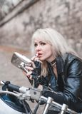 Elegancka blond kobieta pozuje z motocyklem zdjęcia royalty free