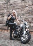 Elegancka blond kobieta pozuje z motocyklem obrazy royalty free