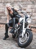 Elegancka blond kobieta pozuje z motocyklem fotografia royalty free
