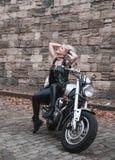 Elegancka blond kobieta pozuje z motocyklem zdjęcie royalty free