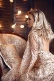 Elegancka blond kobieta w beżu smokingowy pozować na luksusowej kanapie w królewskim wnętrzu Fasonuje pięknej zmysłowej panny mło zdjęcie royalty free