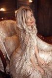 Elegancka blond kobieta w beżu smokingowy pozować na luksusowej kanapie w królewskim wnętrzu Fasonuje pięknej zmysłowej panny mło zdjęcie stock