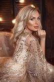 Elegancka blond kobieta w beżu smokingowy pozować na luksusowej kanapie w królewskim wnętrzu Fasonuje pięknej zmysłowej panny mło fotografia stock
