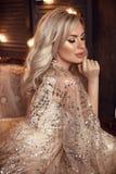 Elegancka blond kobieta w beżu smokingowy pozować na luksusowej kanapie w królewskim wnętrzu Fasonuje pięknej zmysłowej panny mło zdjęcia royalty free