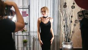 Elegancka blond kobieta w koktajl sukni pozuje dla fotografa w ubraniowym butiku zbiory
