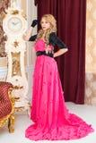 Elegancka blondynka w długiej czerwieni sukni stoi w pokoju Obraz Stock