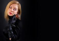 Elegancka blondynki kobieta pozuje w czerni sukni studio Obrazy Stock