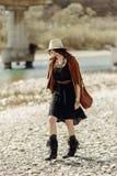 Elegancka boho gypsy kobieta w kapeluszu, krana poncho i butów chodzić, Obrazy Royalty Free