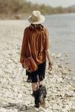 Elegancka boho gypsy kobieta w kapeluszu, krana poncho i butów chodzić, Fotografia Royalty Free