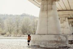 Elegancka boho kobieta pozuje przy rzeką pod kamienia mostem, tylny widok Obraz Royalty Free