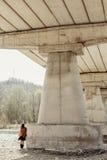 Elegancka boho kobieta pozuje przy rzeką pod kamienia mostem, tylny widok Obrazy Stock