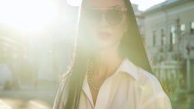 Elegancka brunetka w białej koszula pozuje dla kamery w ranku słońca promieniach zbiory