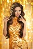 Elegancka brunetka w złotej sukni czarnooki twarzy seksowna kobieta stylowa mody Piękna makeup a Obraz Stock