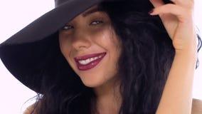 Elegancka caucasian brunetka w kapeluszu przy białym tłem zbiory wideo