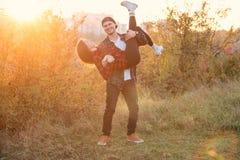 Elegancka caucasian para ubierał przypadkowych ubrania ma zabawę na gazonie w parku Odważny młody człowiek trzyma jego ukochanego zdjęcie royalty free