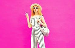 elegancka chłodno dziewczyna w lata round słomianym kapeluszu, biały pasiasty kombinezon z plecakiem na kolorowej menchii ścianie zdjęcie stock