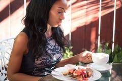 Elegancka ciemnoskóra kobieta ma śniadanie na tarasie a Zdjęcia Royalty Free