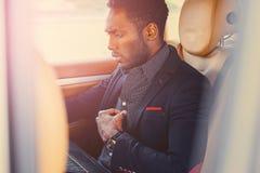 Elegancka Czarna samiec w samochodzie używać laptop obraz royalty free
