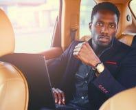 Elegancka Czarna samiec w samochodzie używać laptop fotografia royalty free