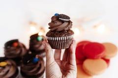 Elegancka czekoladowa babeczka w ręce z ciastkiem i cukierkiem na wierzchołku zdjęcie stock