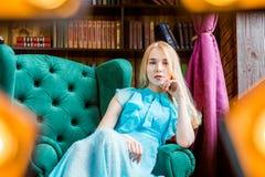 Elegancka dama jest ubranym błękita smokingowego obsiadanie w krześle w bibliotece Piękno, moda Obrazy Stock