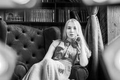 Elegancka dama jest ubranym błękita smokingowego obsiadanie w krześle w bibliotece Piękno, moda Zdjęcie Stock