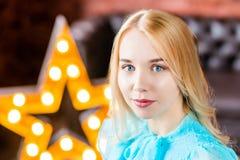 Elegancka dama jest ubranym błękita smokingowego obsiadanie w loft studiu z gwiazdą behind Piękno, moda Zdjęcie Stock