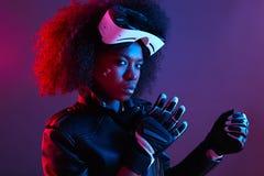Elegancka kędzierzawa ciemna z włosami dziewczyna ubierał w czarnych skórzanej kurtki i rękawiczek pozach z rzeczywistość wirtual zdjęcie stock