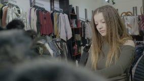 Elegancka klient dziewczyna wybiera podstawowych kawałki odzież dla jej jesieni zimy garderoby w centrum handlowe sklepie - zbiory
