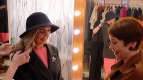 Elegancka kobieta próbuje rzemienne rękawiczki w mody sali wystawowej podczas gdy robiący zakupy Starsza kobieta wybiera nowe ręk zdjęcie wideo